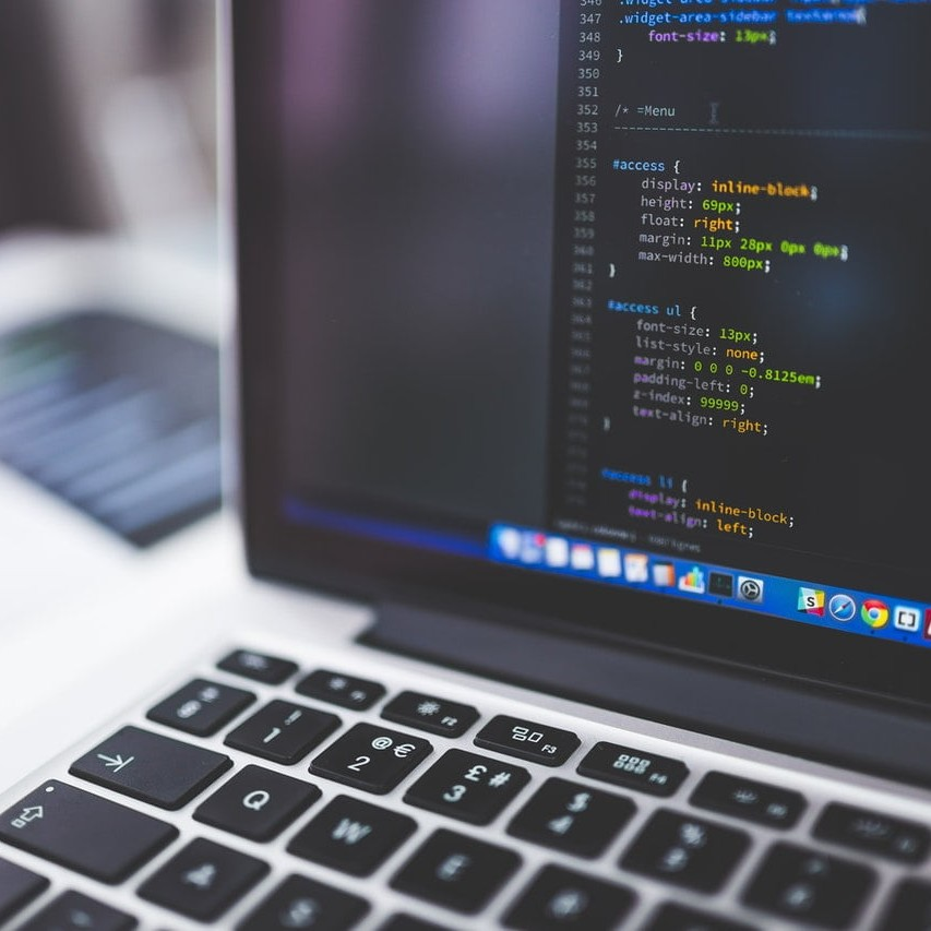 Coding the CSS for a website design on laptop.